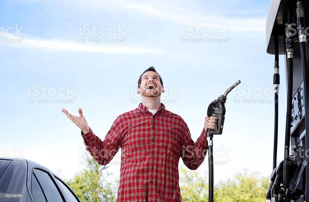 Man at gas pump completely frustrated with the increased prices royalty-free stock photo