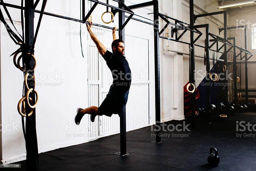 Man at gym exercise Kipping pull-ups stock photo