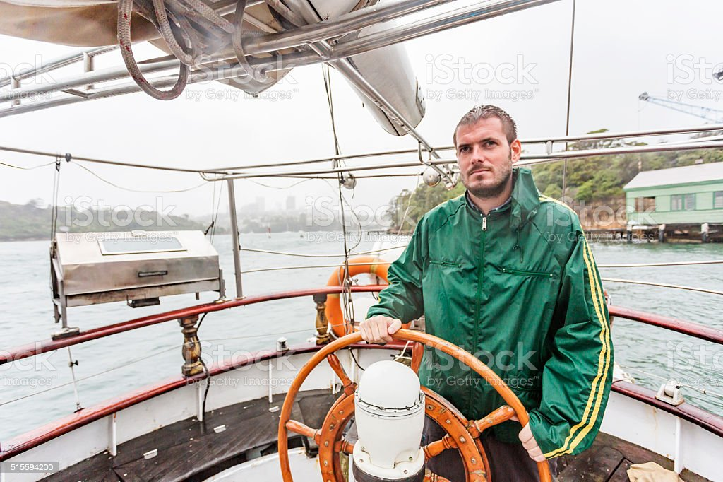 Man At Helm of Yacht During a Sydney Storm stock photo