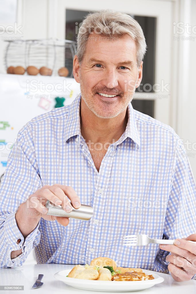 Man At Home Adding Salt To Meal stock photo