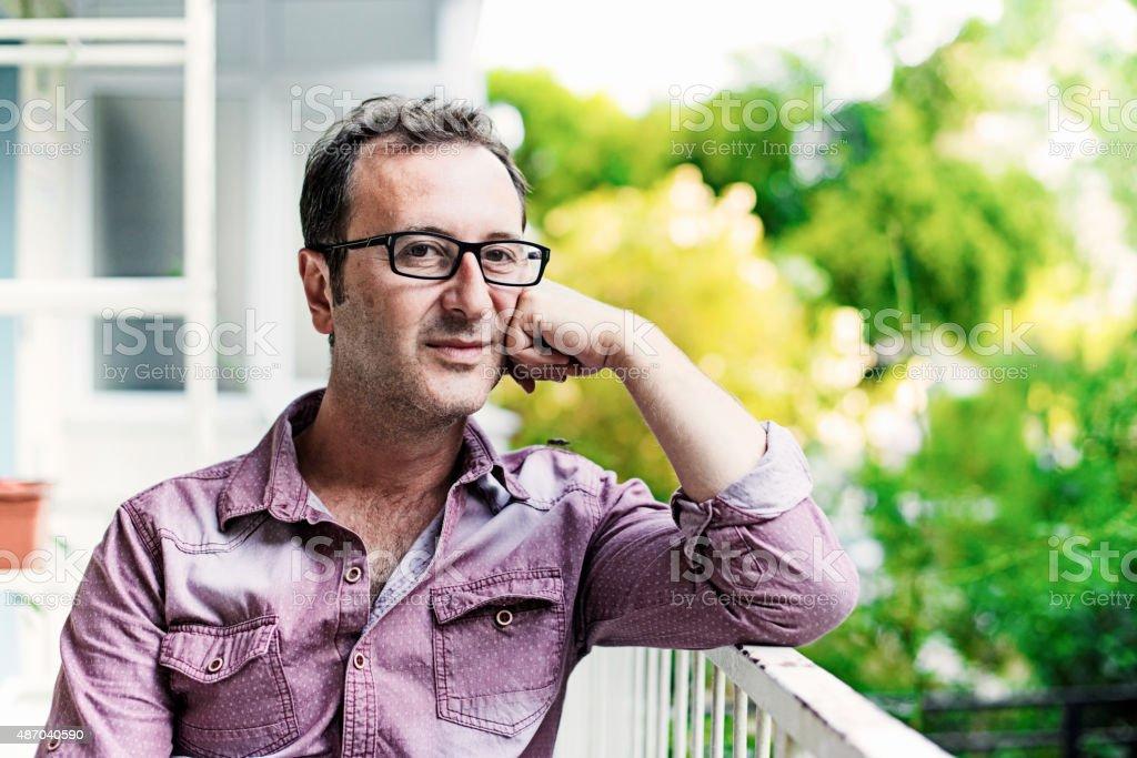 Man at Home at Balcony - Thinking and Positive stock photo