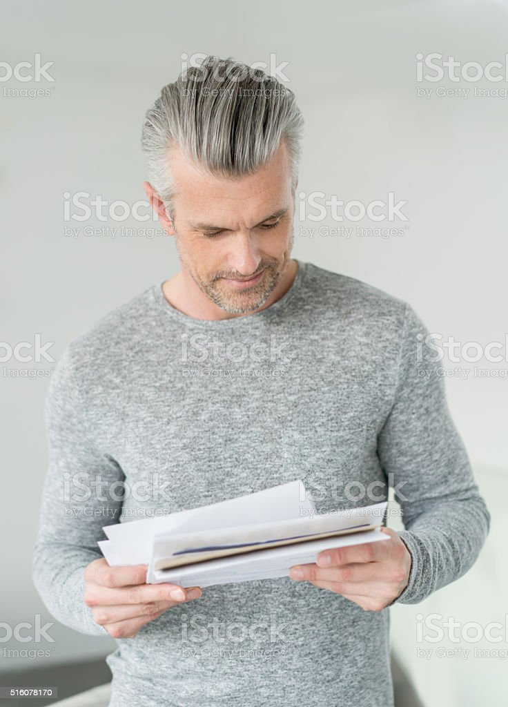 Man at home getting the mail stock photo
