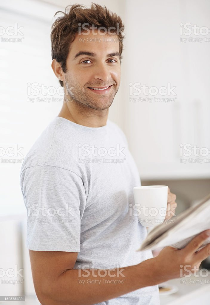 Man at home holding newspaper and coffee royalty-free stock photo