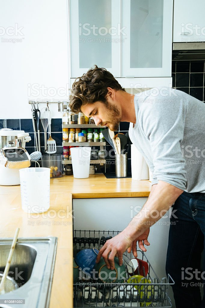 Man At Home Loading The Dishwasher stock photo