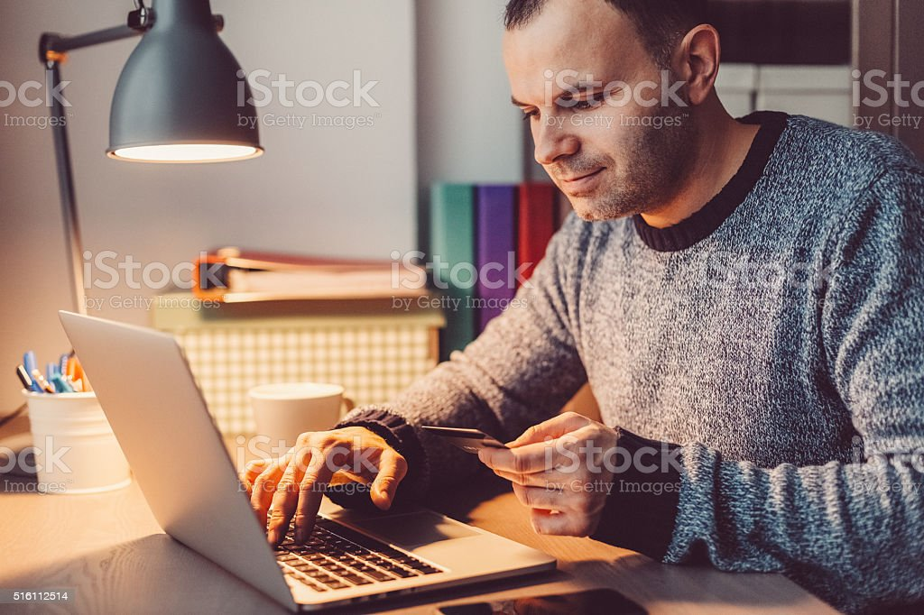 Man at home shopping online with credit card stock photo