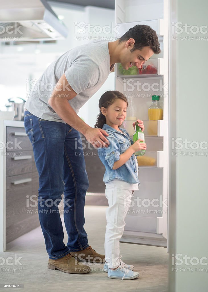 Man at home with his kid opening the fridge stock photo