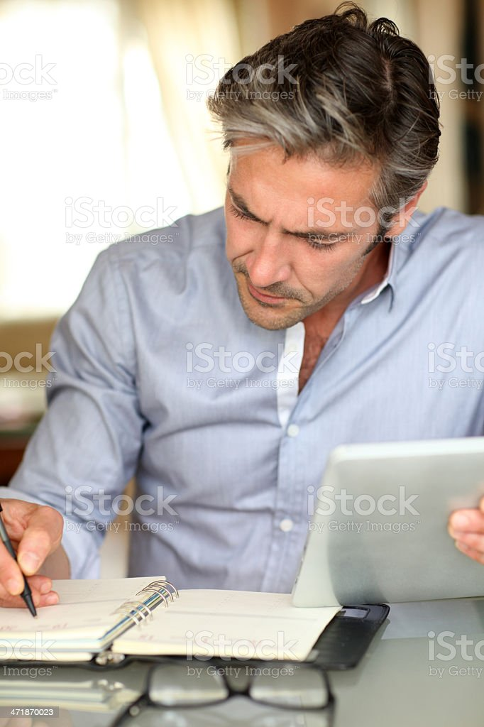 Man at home writing on agenda with tablet in hand royalty-free stock photo