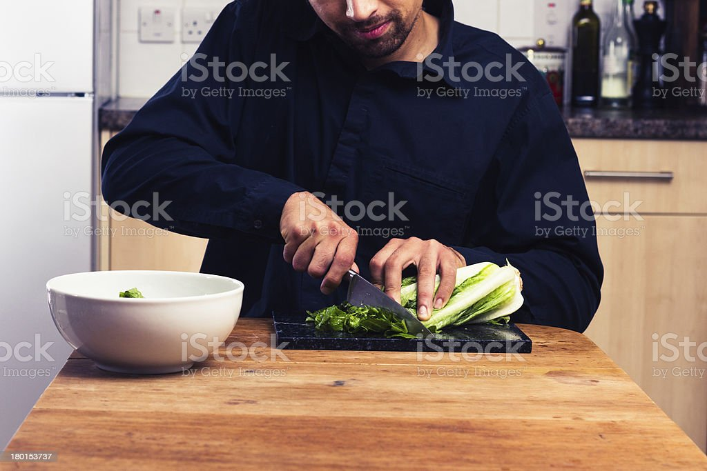 Man at kitchen table chopping lettuce royalty-free stock photo