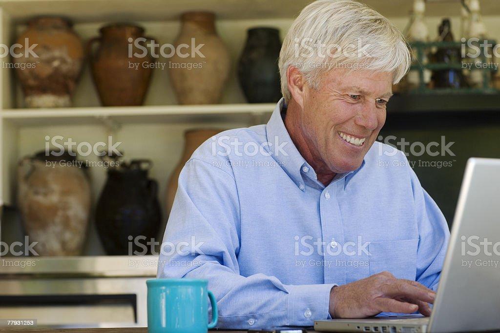 Man at laptop with mug smiling royalty-free stock photo