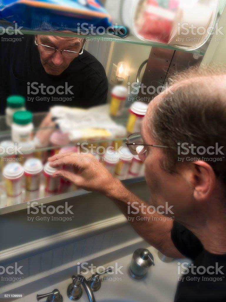man at medicine cabinet stock photo