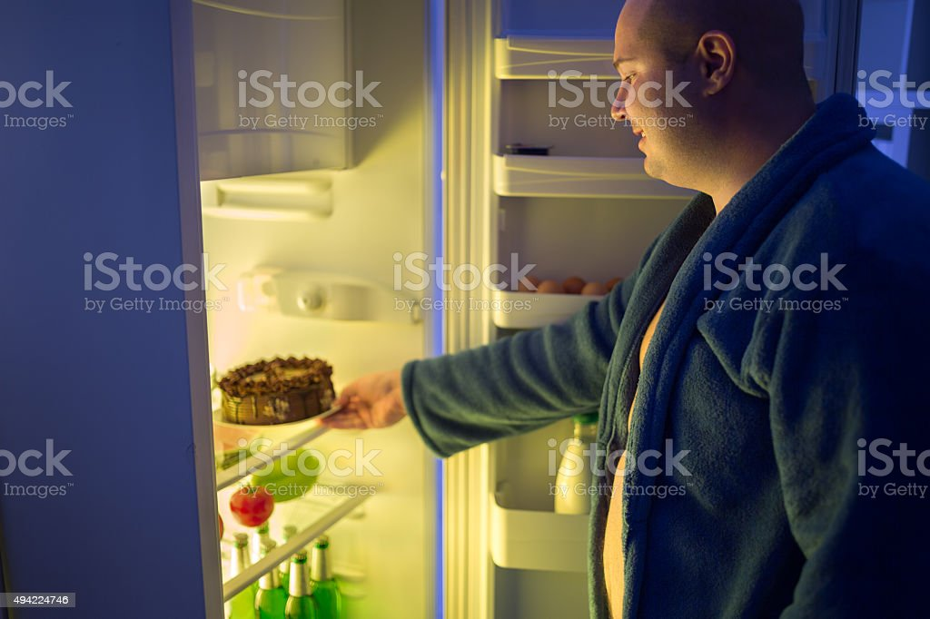 Man at night overstep and take whole chocolate cake stock photo