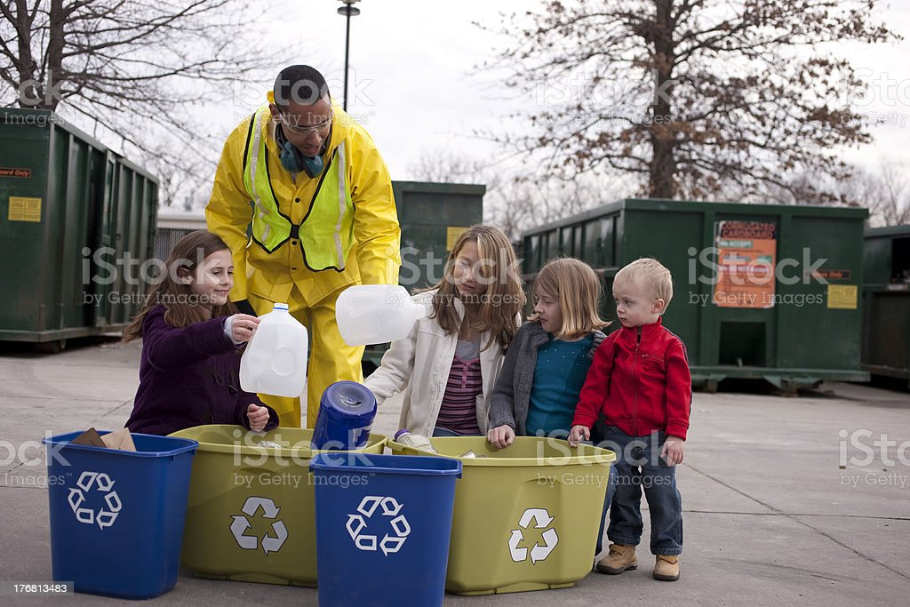 Man at Recycling Center Helps Children Sort Trash stock photo