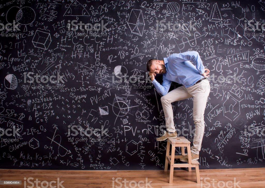 Man at step ladder, against big blackboard, formulas, symbols stock photo