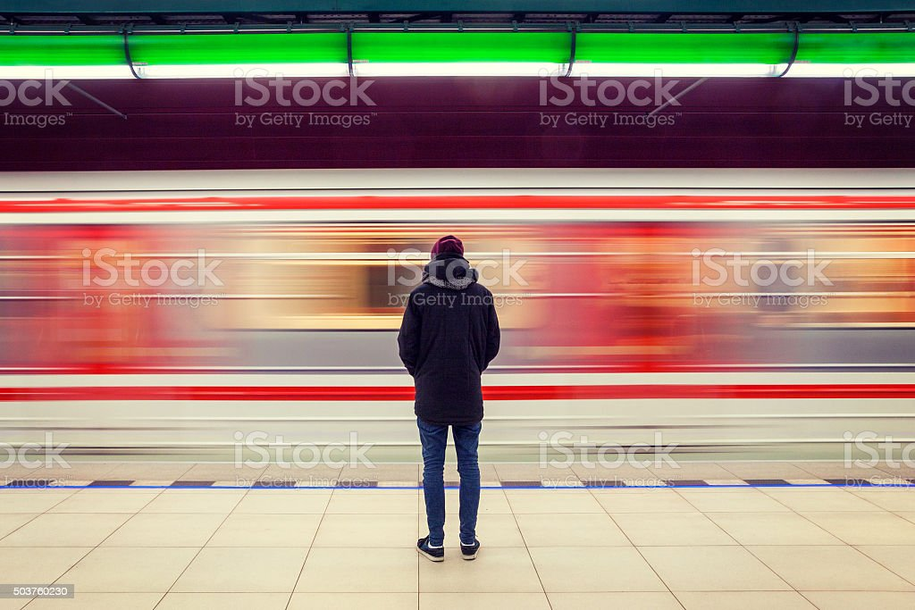Man at subway station and moving train stock photo
