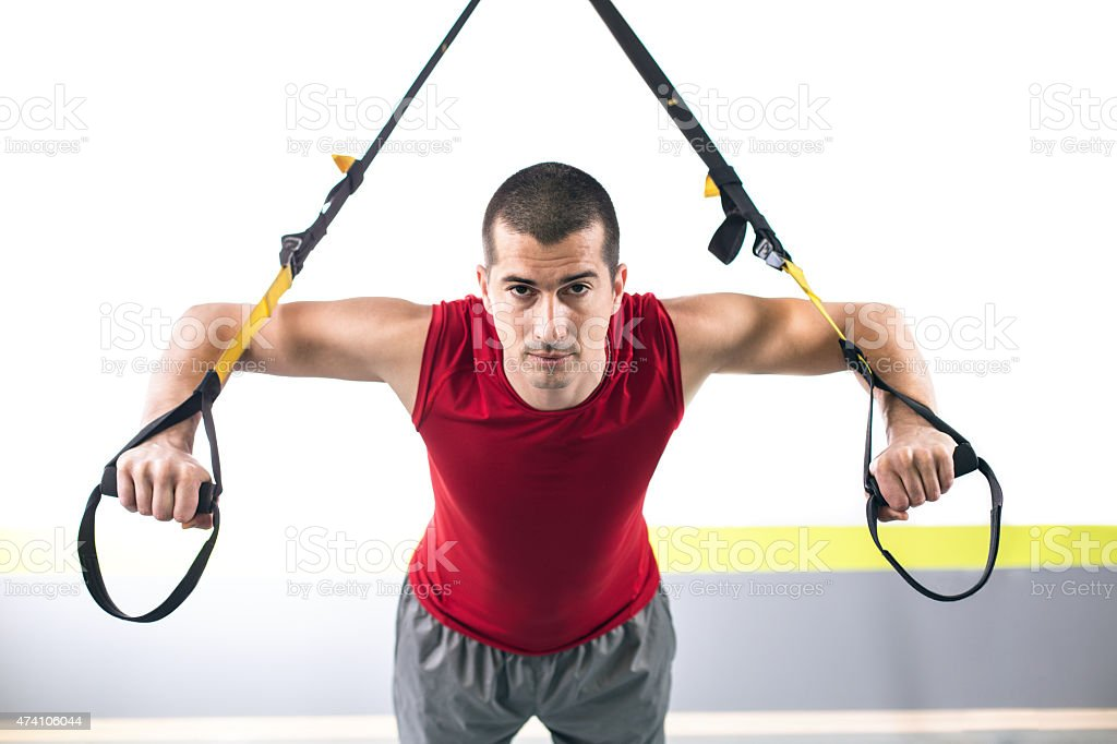 Man at suspension training in gym stock photo