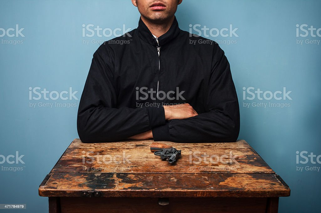 Man at table with gun royalty-free stock photo