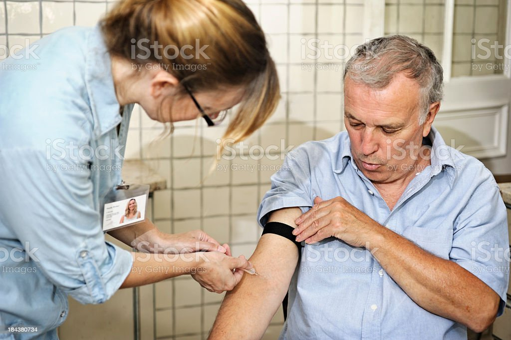 Man at the doctors getting his blood taken by a nurse stock photo