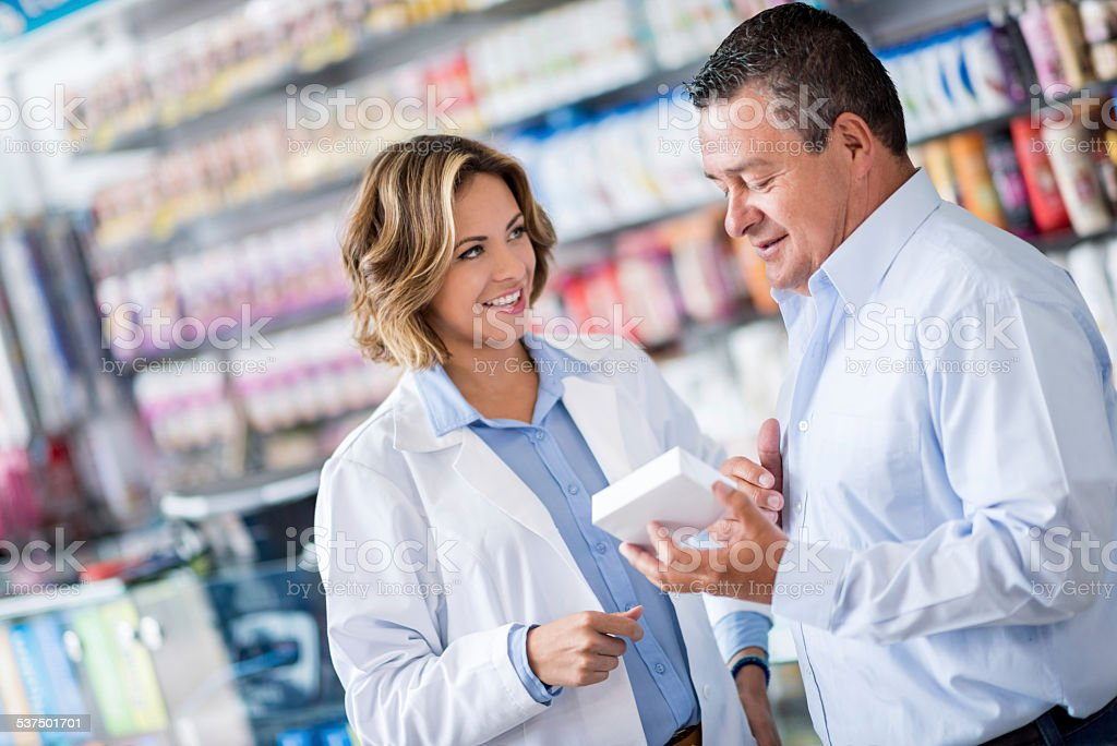 Man at the drugstore asking pharmacist for advice stock photo