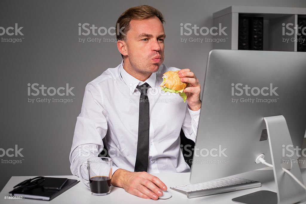 Man at the office eating burger stock photo