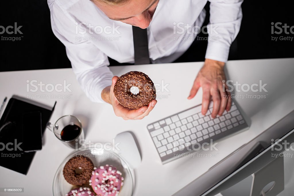 Man at the office eating donuts stock photo