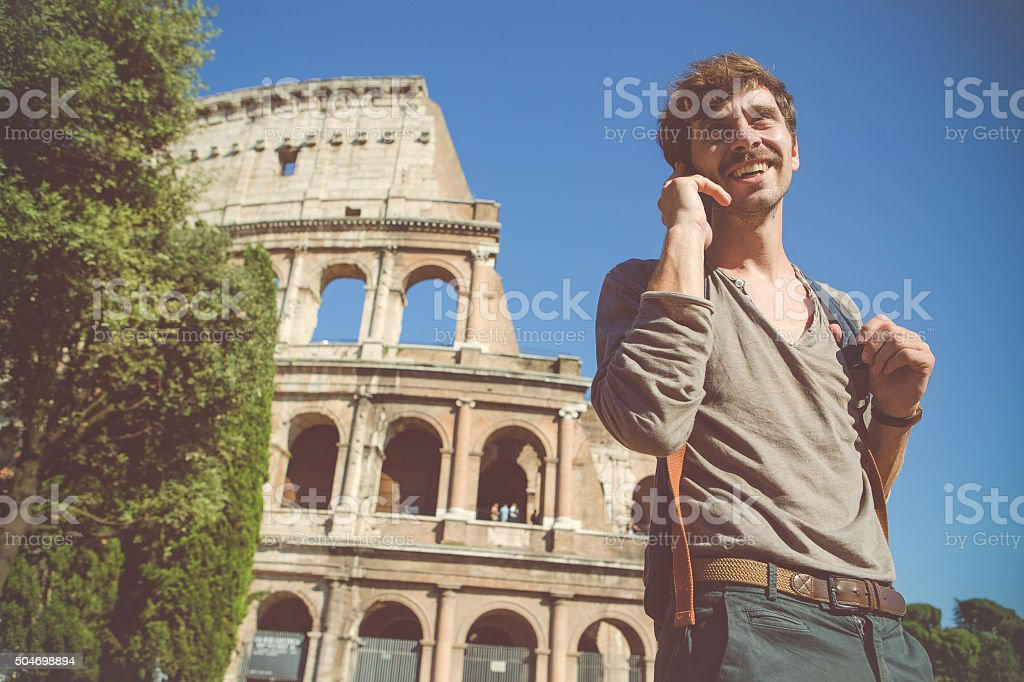 Man at the telephone under the Coliseum in Rome stock photo