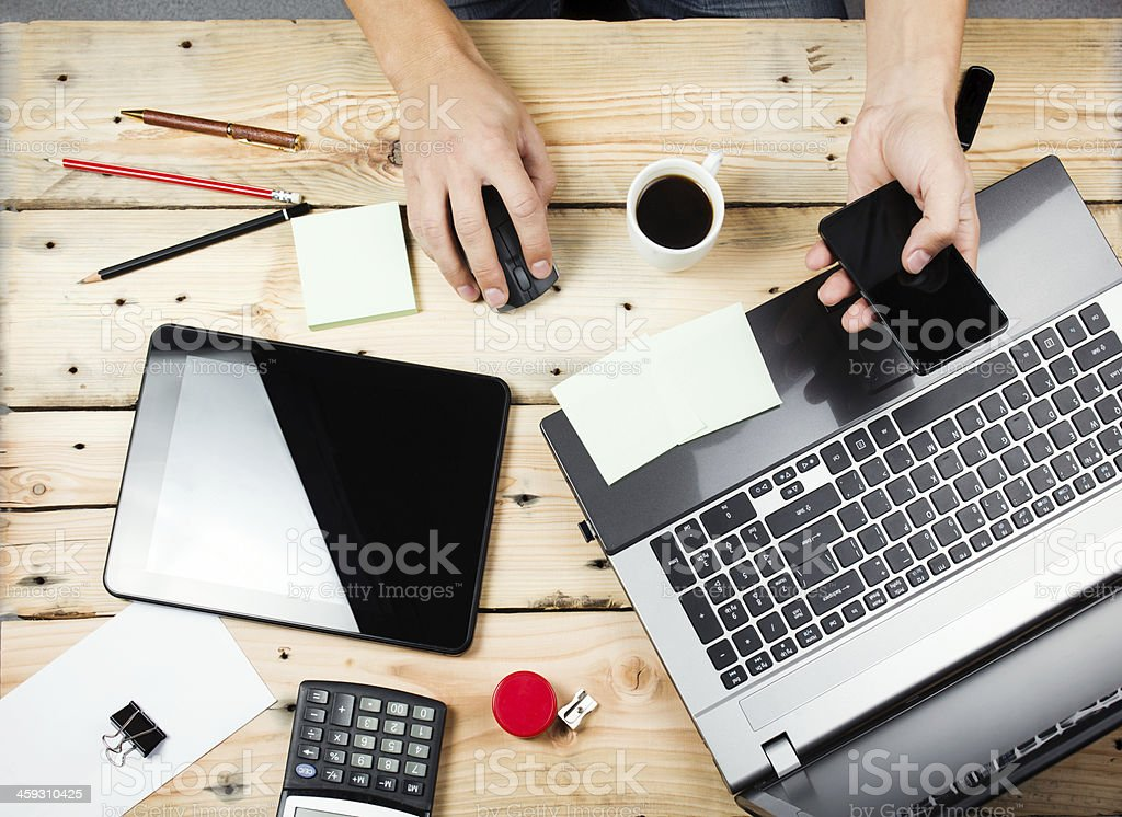 Man at wooden table with laptop and smartphone stock photo