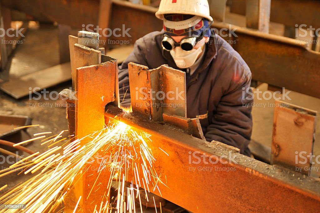 A man at work using a torch to cut metal stock photo