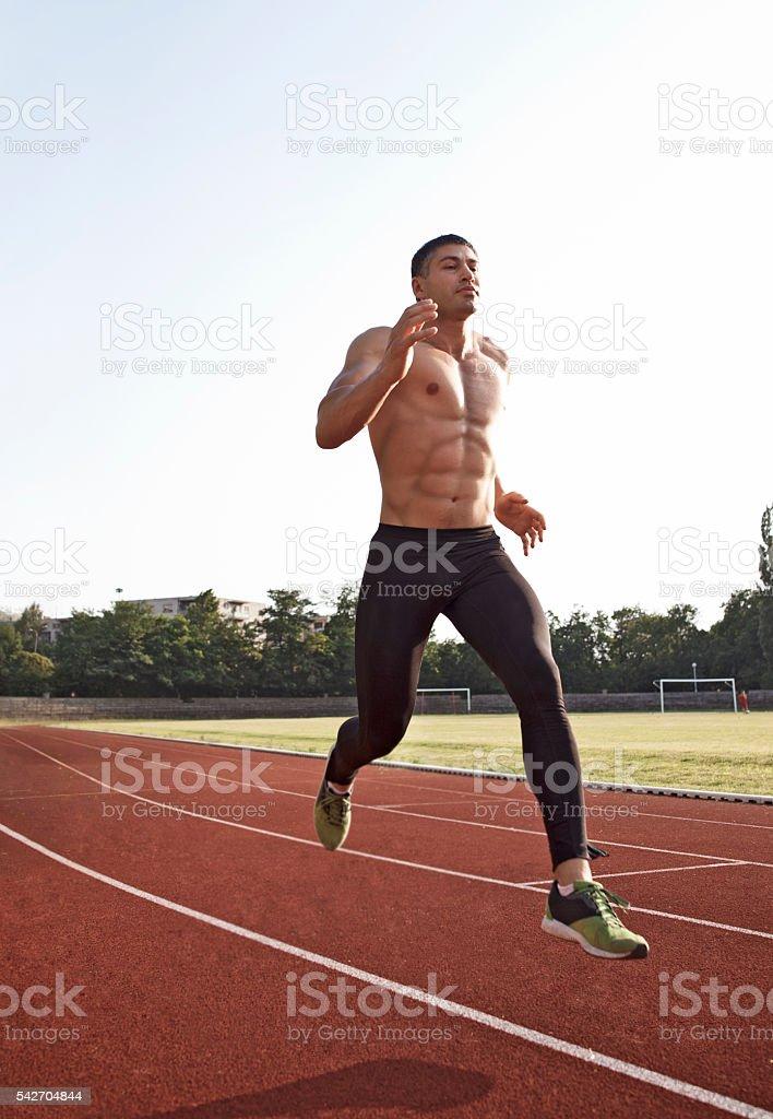 man  athlete training on a race track stock photo