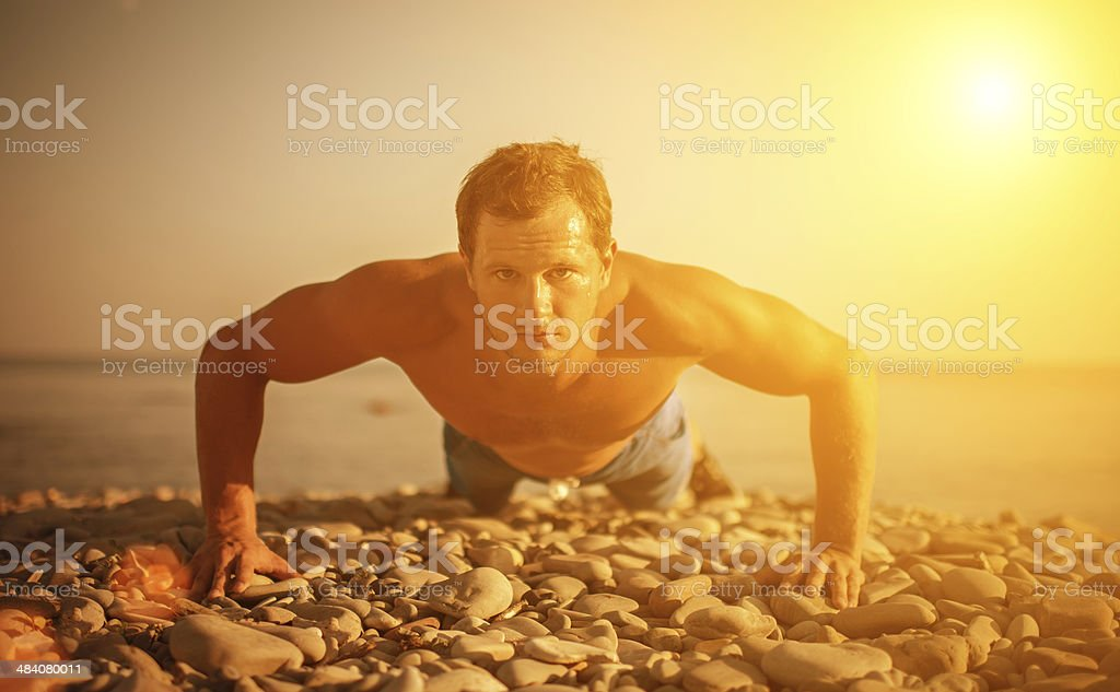 man athlete trains, practicing, pushed on  beach royalty-free stock photo