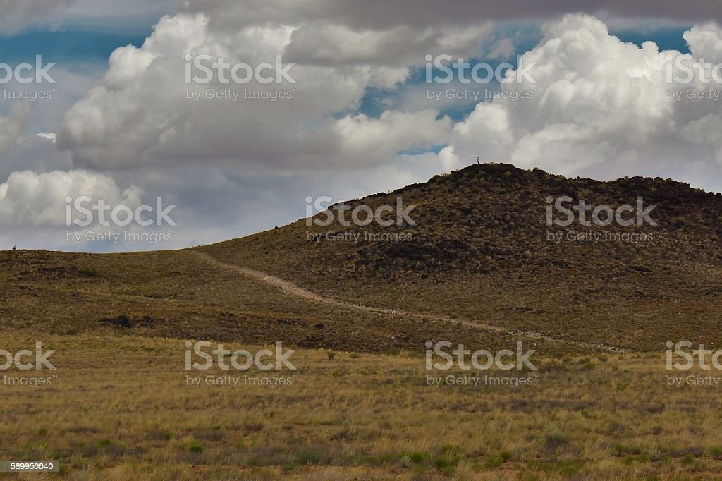 Man Atop Distant Hill stock photo