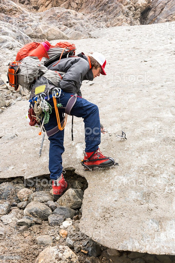 Man attaches crampons to boots stock photo