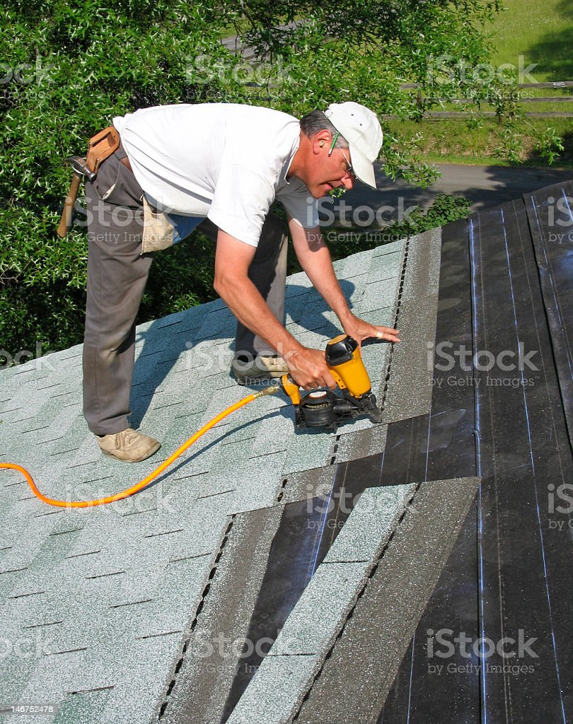 Man attaches shingles to roof stock photo