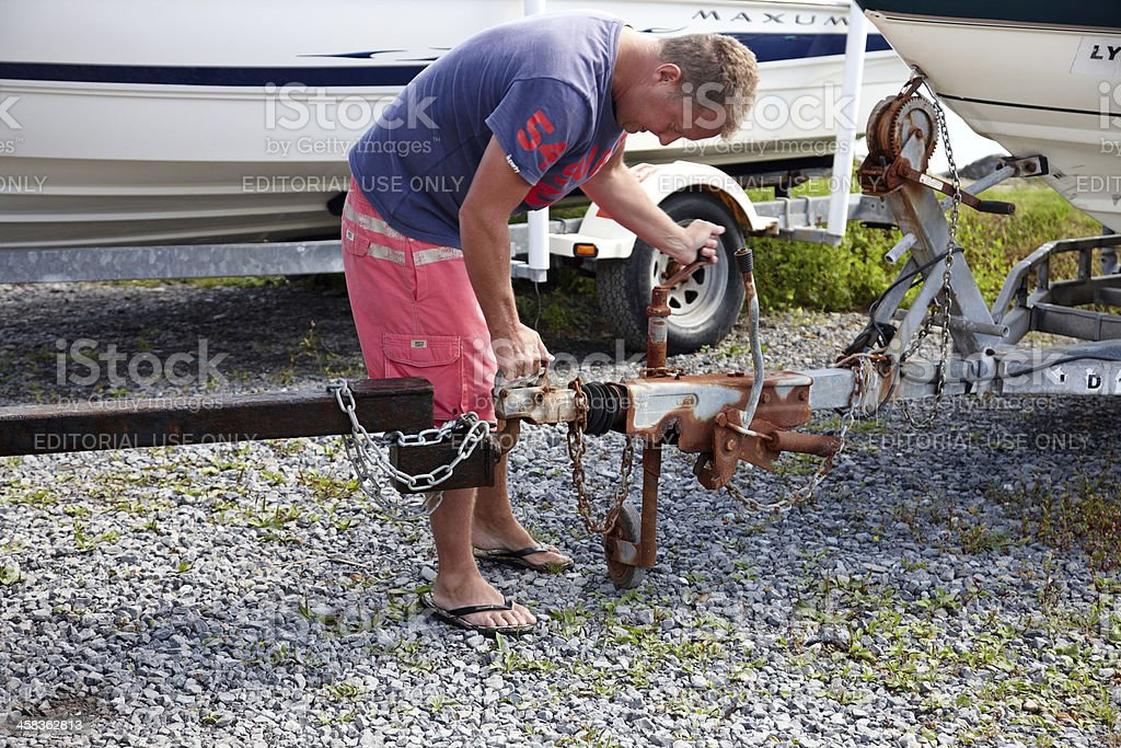 Man attaching towbar hitch to boat trailer stock photo