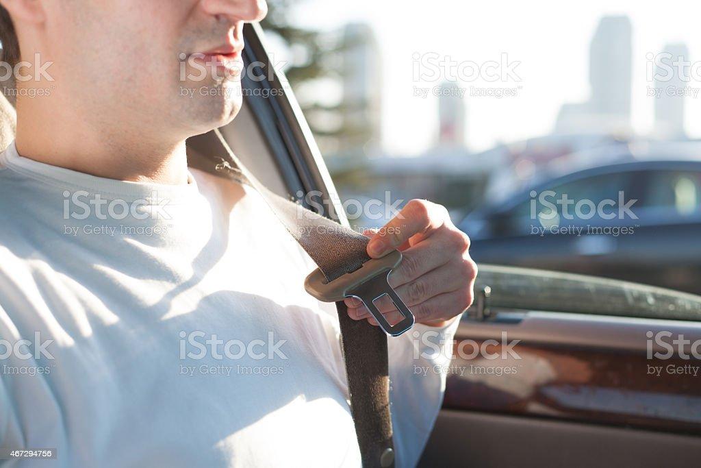 Man attempting on put on his seatbelt stock photo
