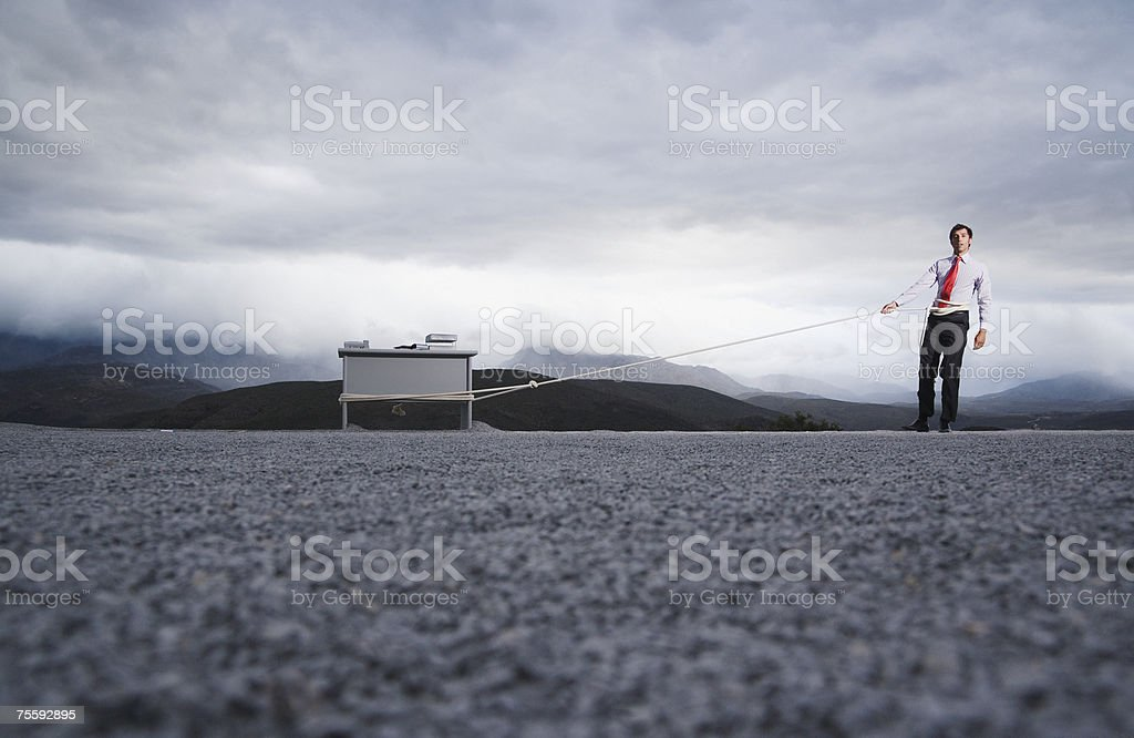 Man attempting to pull his desk outdoors with a long rope royalty-free stock photo