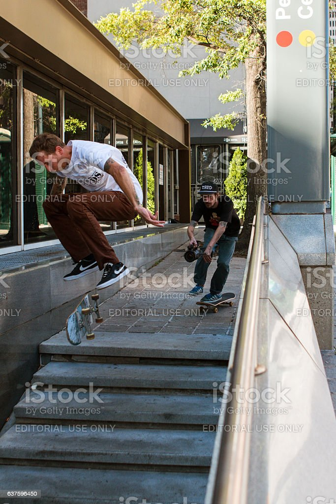 Man Attempts Difficult Skateboard Trick While Being Filmed stock photo