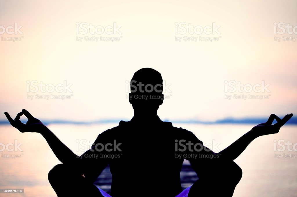 man backlight making yoga in front of the sea stock photo
