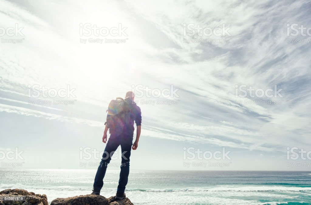 Man backlit in sunflare above the coast of South Cornwall. stock photo