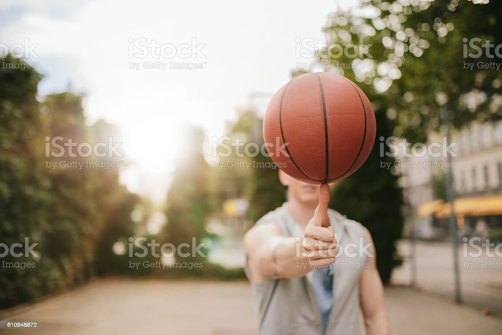 Man balancing basketball on his thumb stock photo