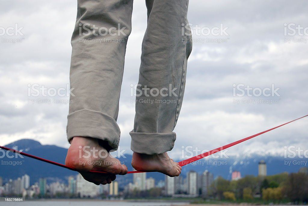Man balancing on a red tightrope in bare feet stock photo