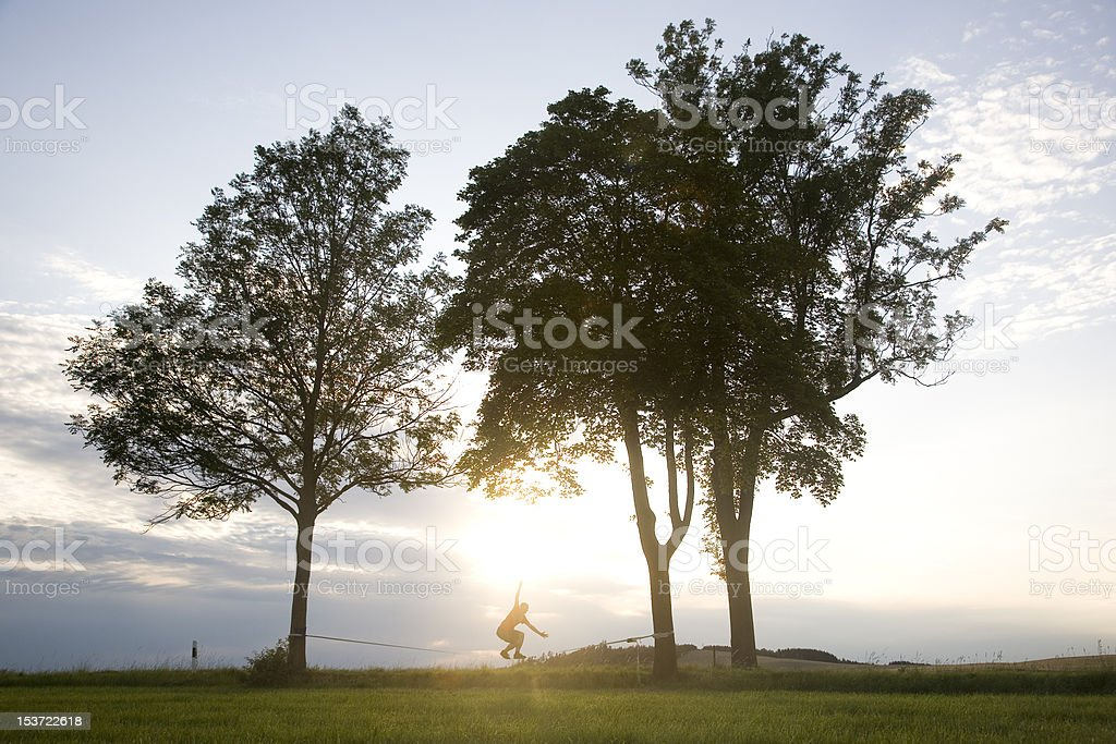 man balancing on a slackline stock photo
