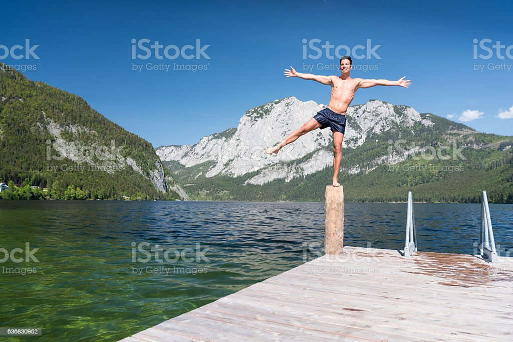 Man balancing on one leg, Lake Altaussee, Austria stock photo