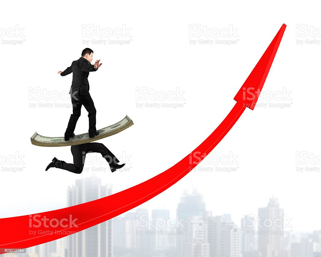 Man balancing running money legs on red arrow up stock photo