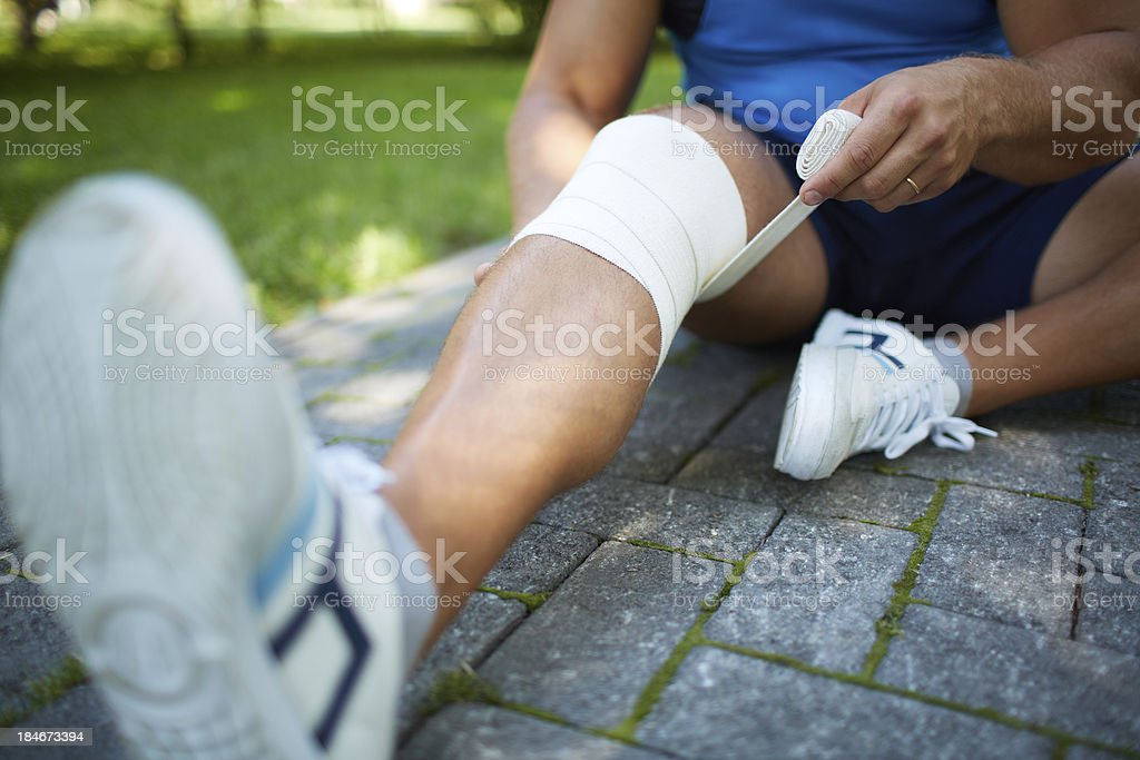Man bandaging his knee for support during sport practice royalty-free stock photo
