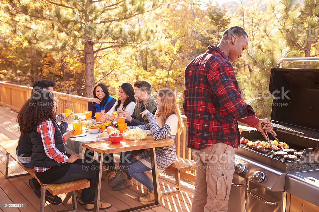 Man barbecues for friends at a table, on a deck in stock photo