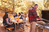 Man barbecues for friends at a table, on a deck in