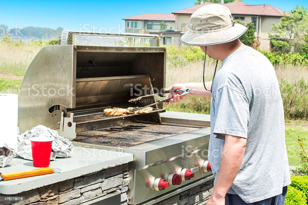 Man barbecuing chicken on a outdoor gas grill stock photo