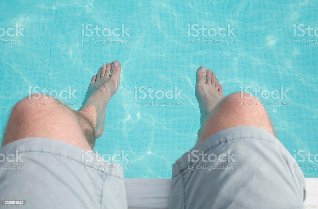 Man barefoot at swimming pool. stock photo