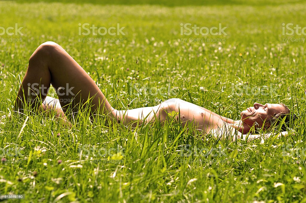 Man basks in the grass stock photo