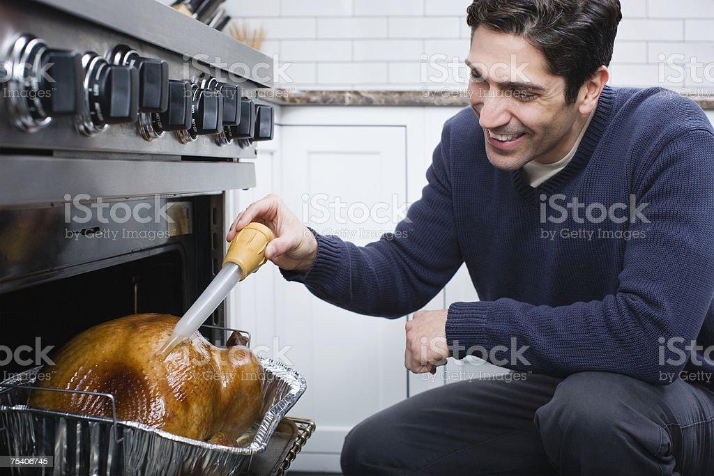 Man basting turkey stock photo